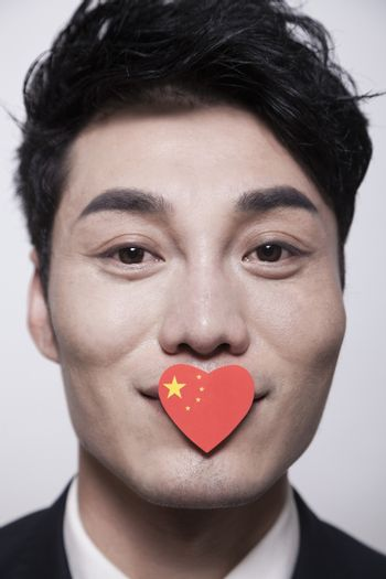 Young businessman looking at the camera with a heart shaped Chinese flag covering his mouth