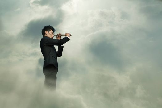 Young businessman looking through telescope in a dreamlike cloud