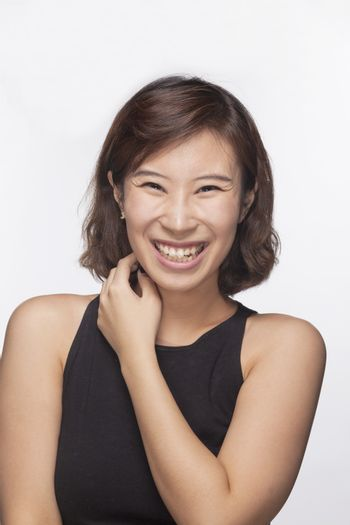 Smiling and happy young woman, portrait, studio shot