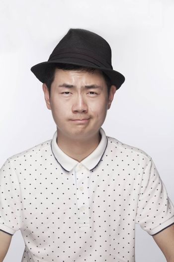 Portrait of serious young man wearing a hat, studio shot