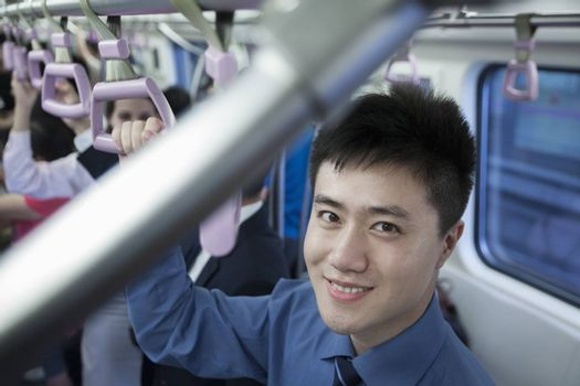 Portrait of smiling young businessman standing on the subway, looking at camera
