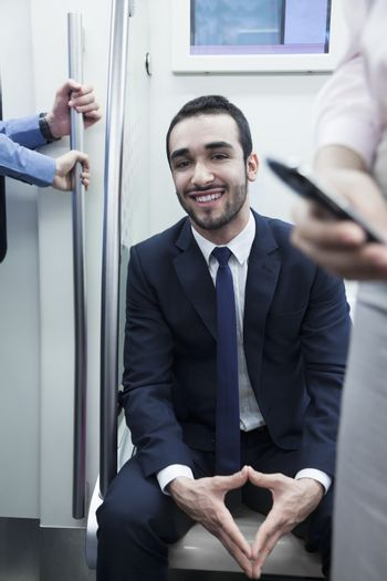 Portrait of young smiling businessman sitting on the subway and looking at camera