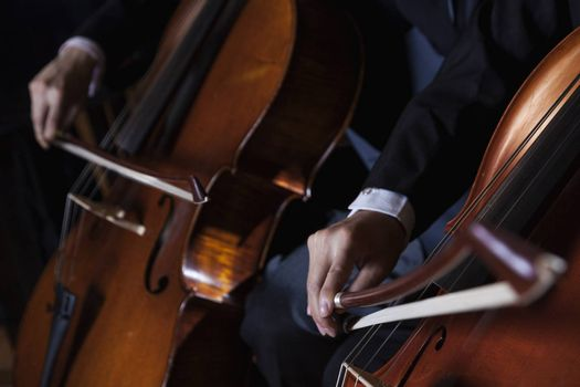 Close-up of midsection of two cellists playing the cello during a performance