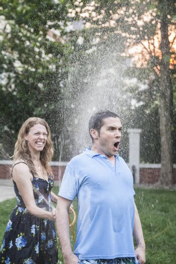 Couple playing with a garden hose and spraying each other outside in the garden, man has a shocked look