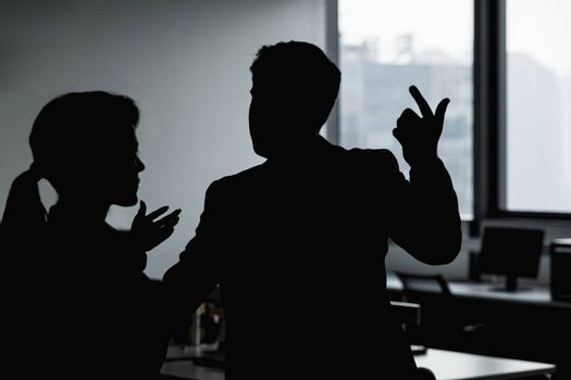 Silhouette of two business people gesturing and arguing in the office