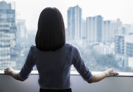 Rear view of a businesswoman looking out the window at the cityscape in Beijing, China