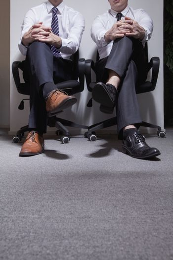 Two businessmen sitting down with legs crossed, low section