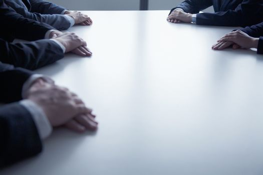 Close-up on folded hands of business people at the table during a business meeting