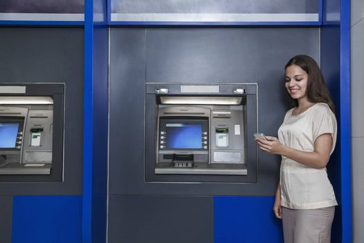 Smiling young woman standing in front of an ATM and looking at her phone
