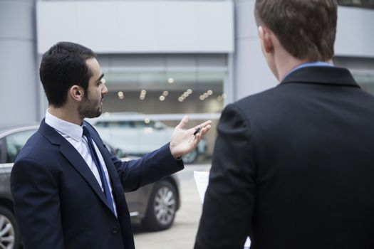 Car salesman holding car keys and selling a car to a young businessman