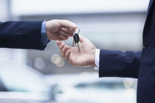 Car salesman handing over the keys for a new car to a young businessman, close-up
