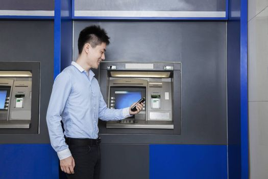 Smiling young businessman standing in front of an ATM and looking at his phone