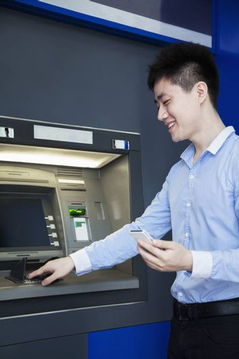 Smiling young businessman withdrawing money from the ATM