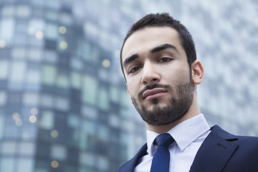 Portrait of serious young businessman, outdoors, business district