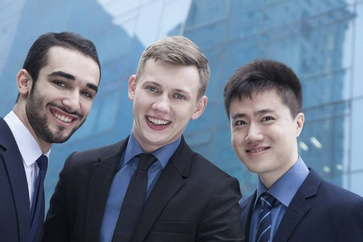 Portrait of three smiling businessmen, outdoors, business district