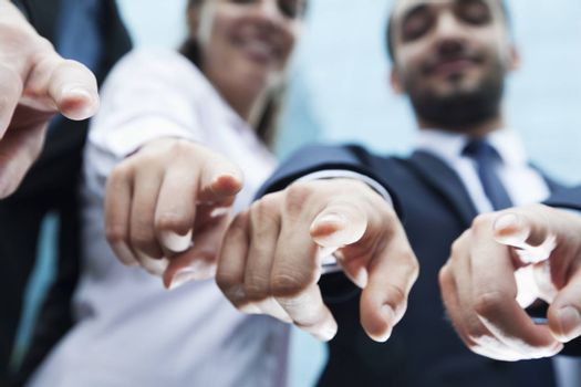 Close-up of four business people's fingers pointing at camera