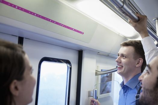 Three business people standing on the subway and looking at the map
