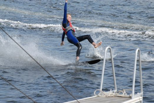 Boy falling on water skis