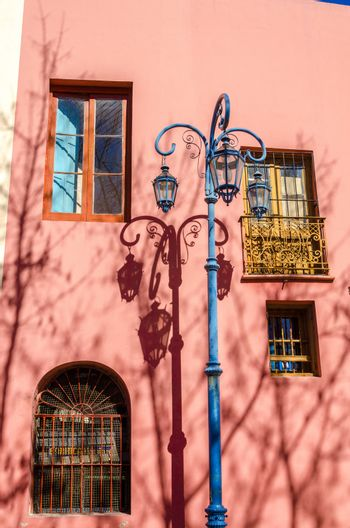 Blue streetlight in La Boca neighborhood of Buenos Aires next to a pink building