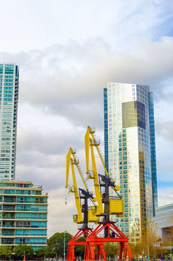 Modern skyscraper in Puerto Madero neighborhood of Buenos Aires with old colorful cranes