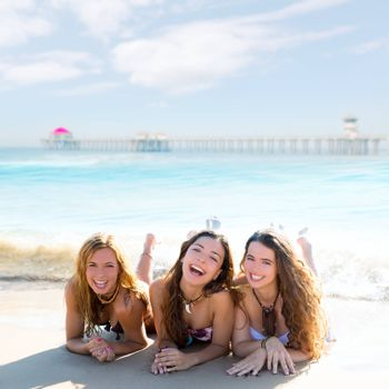 happy three teen friends girls lying on beach sand smiling at Huntington Beach California