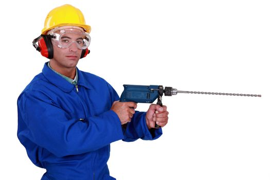 craftsman with earmuffs and protective goggles holding electric drill