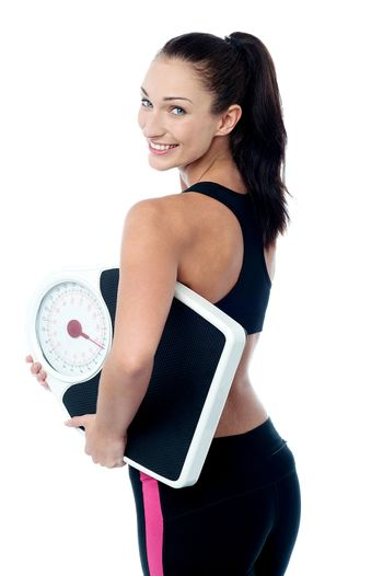 Female fitness trainer holding weighing machine