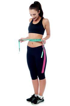 Slim fit woman measuring her waist