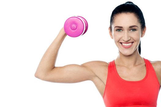 Woman in gym working out with dumbbell