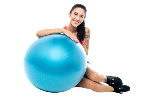 Woman in gym relaxing beside exercise ball