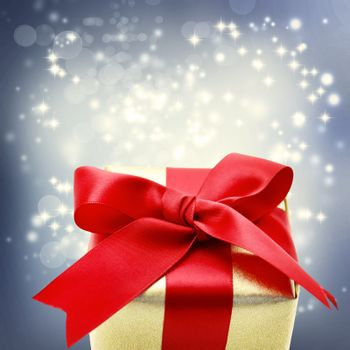 Golden gift box with big red ribbon