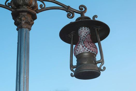 Lamp on a pole on the street, made in the form of antique lamp. Photographed on the background of blue sky.