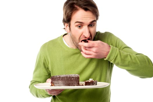 Young man tasting chocolate cake in hurry