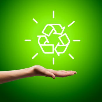 Recycling symbol in human hand against green background