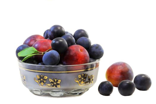 Large ripe plums and prunes in a vase for fruit. Presented on a white background.