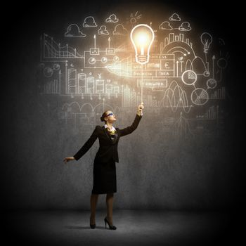Image of businesswoman holding bulb balloon with sketch at background