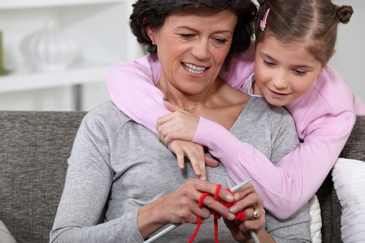 A mom showing how to knit to her daughter.