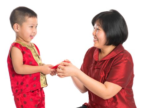 Asian Chinese boy receiving red paper packet or monetary from parent on Chinese New Year festival, with traditional Cheongsam isolated on white background.