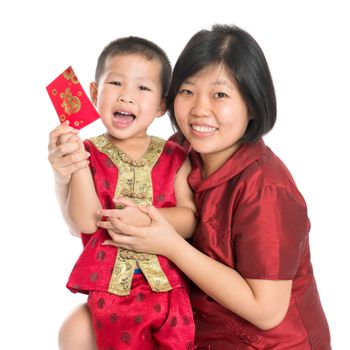 Asian Chinese child receiving monetary gift or red paper packet from parent on Chinese New Year festival, with traditional Cheongsam isolated on white background.