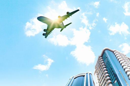 Image of airplane flying above skyscrapers. Bottom view