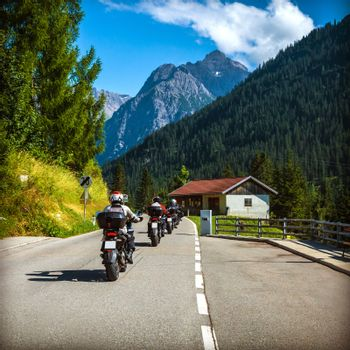 Group of bikers on the road in Alps