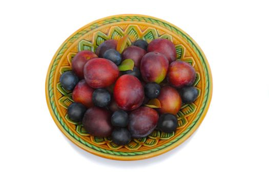 Large ripe purple plums and prunes in a ceramic dish . Presented on a white background.