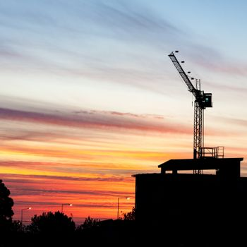 A construction crane silhouetted at sunset. (square frame)