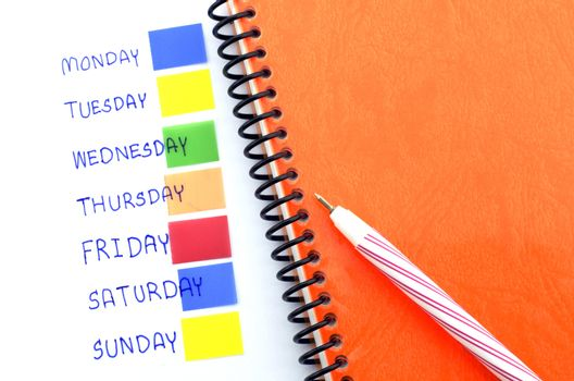 orange notebook red pen and post it monday to sunday