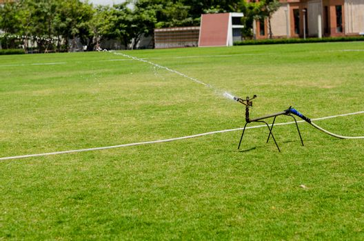 watering in football field on day