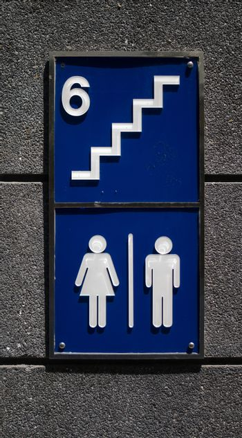 toilet sign on wall at public street