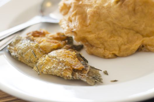 fried fish and omelet in dish with spoon and fork