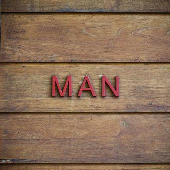 man toilet symbolic on wood background texture