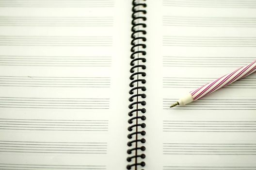 music notebook and red pen ready to wite your own song