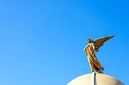 An angel on top of a tomb in the Recoleta Cemetery in Buenos Aires